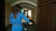 Back view of a brunette girl with long hair walking with a bike into old gate in old town, slow mo, steadicam shot video
