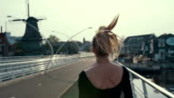 Back view of a female silhouette running at sunset on a bridge in Holland, slow motion. video