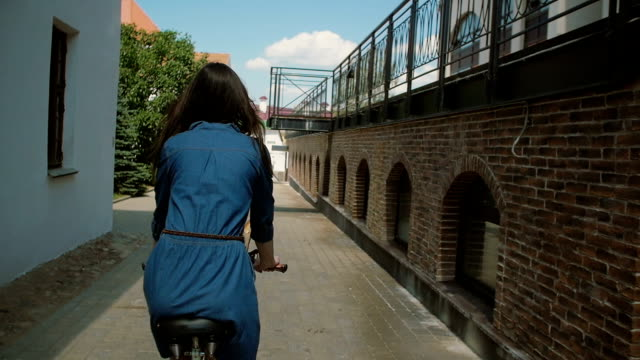 Back view of a girl in a dress riding a bike with flowers in basket in the street in summertime, slow mo, steadicam shot video