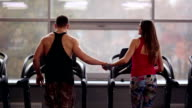 Back view of a sporty couple. Man is reaching his hand to the woman, she gives her hand to him. They run on treadmills video