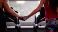 Back view of a sporty couple running on treadmills holding hands. Close-up of hands. Working out in a gym video
