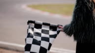 Back view of a woman is holding a waving race checkerd flag. Go-kart track video