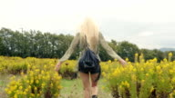 Back view of beautiful blond young girl walks outdoor in nature - gimbal steadicam HD video footage video
