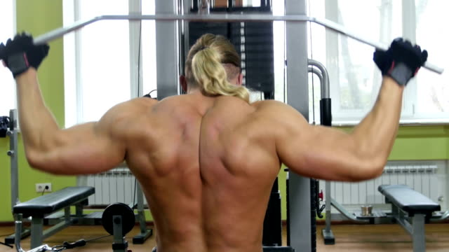 Back view of bodybuilder doing exercises on the trainer video