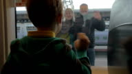 Back view of boy watching in window from rail train and saying goodbye his grandparents, swinging arms video