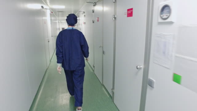 Back view of female doctor in protective uniform walking in hospital corridor video