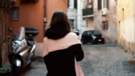 Back view of girl walking alone in old town. Brunette woman going through the street. Female have vacation in Europe video