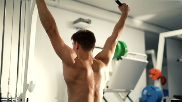 Back view of handsome bodybuilder trains on simulator video
