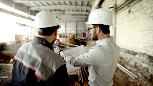 Back view of men in helmets and eyeglasses standing together in construction area with people in the background. Architect and worker looking at structure plan and discussing details of development video