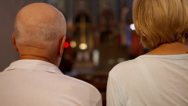 Back view of senior couple sitting in catholic church. Two pensioners ceremony service praying video