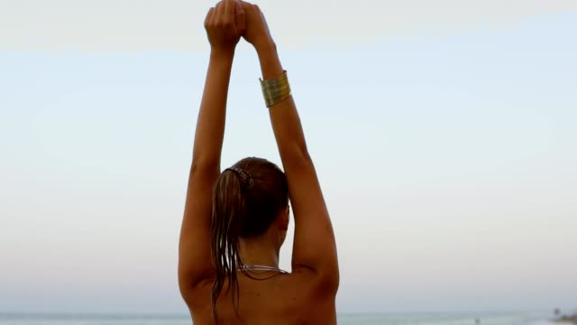 Back view of sexy woman with golden makeup raising up her hands and then turning around and looking in the camera wet ponytail walking by the water on the beach at the evening video