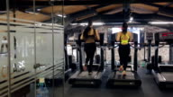 Back view of slim athlete women running on a treadmill in a gym video