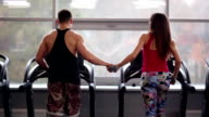 Back view of sporty man and beautiful woman running on treadmills, holding hands. Work out in a sport club video