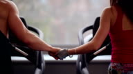Back view of sporty man and beautiful woman running on treadmills, holding hands. Work out in a sport club. Close-up video