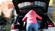 Back view of woman putting shopping bags in car video