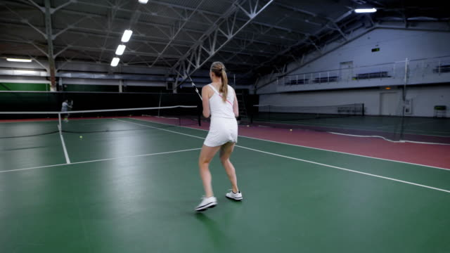 Back view of woman serving and returning bouncing balls with racket. Professional sport players having training at indoor court improving skills. Female instructor teaching man playing tennis video