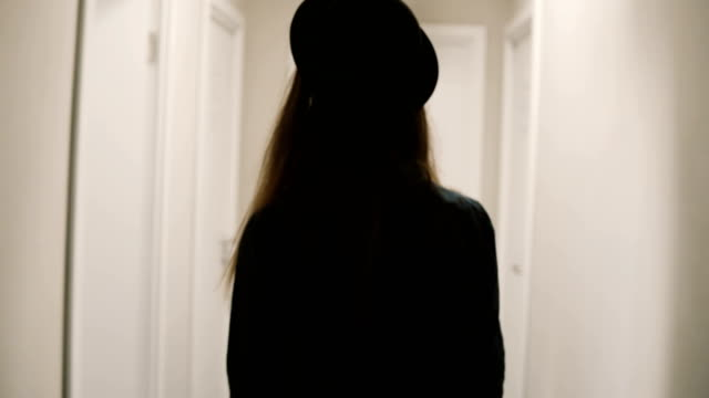 Back view of woman walking through corridor, come in room and puts on knob the door hanger, asking do not disturb her video