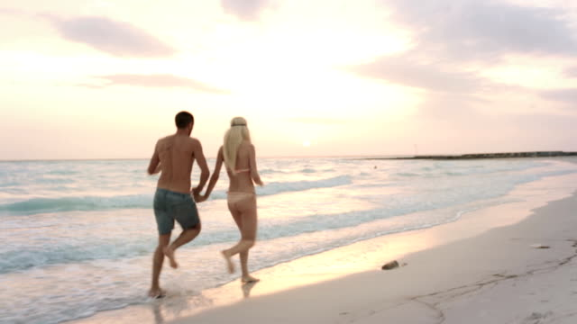 Back view of young man-woman couple in love enjoys and run along ocean beach sea-side at sunrise or sunset in summer - gimbal steadicam HD video footage video