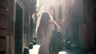 Back view of young woman walking at city street in Europe at morning. Girl exploring the old town alone, looking around video
