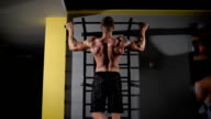 Back view portrait of a muscular man tightening in The Gym's Studio video
