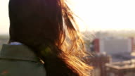 Back view. Wind blows long dark hair beautiful young women. girl standing on the roof at sunset. Slow mo video