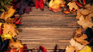 Background with wooden table and autumnal leaves video