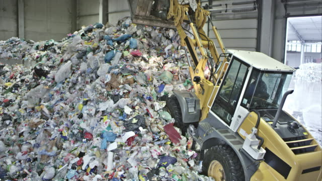 TS backhoe loader piling up plastic waste in recycling facility video
