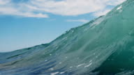 Backlit beautiful wave POV as wave breaks over camera on shallow sand beach in the California summer sun. Shot in slowmo on the Red Dragon at 300FPS. video