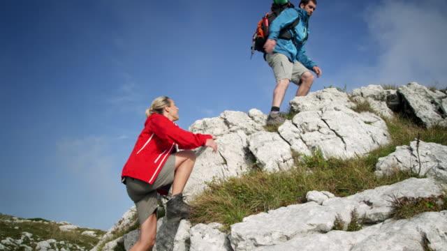 Backpacker climbing a mountain video