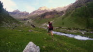 Backpacker hiking in idyllic landscape. Summer adventures and exploration on the Alps, through blooming meadow and green woodland set amid high altitude mountain range. Valle d'Aosta, Italy. video