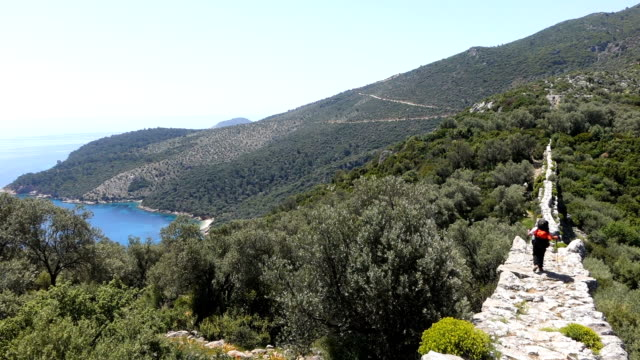 Backpacker is walking on the ancient water arch wall in Kalkan video