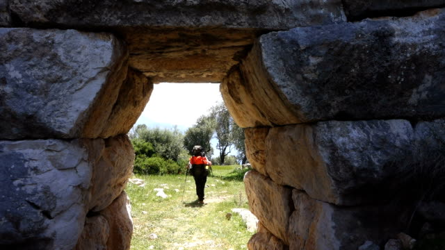 Backpacker is walking through ancient water arch wall in Kalkan video