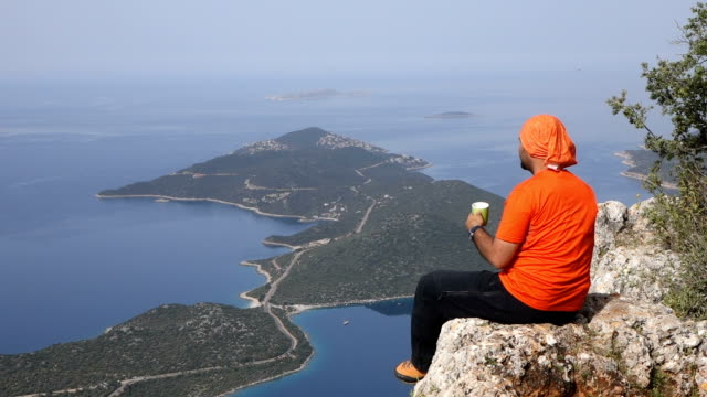 Backpacker is watching the mediterranean sea while drinking coffee video