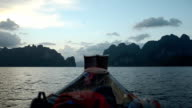 backpacker on boat in Cheow Lan lake at sunset, Thailand video