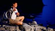 Backpacker walks on rocky coast video