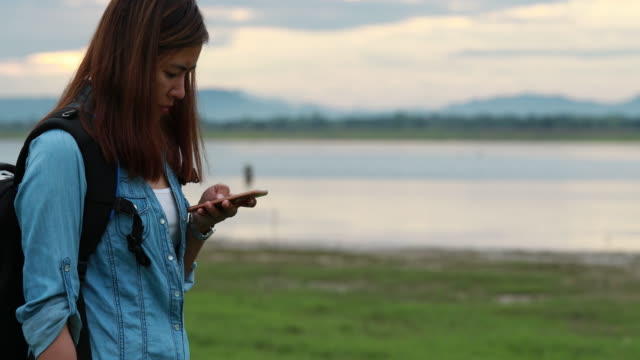 Backpacker woman using smartphone in the nature video