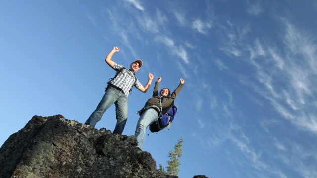 Backpackers celebrate on top of rock video