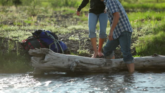 Backpackers roll up pants and put feet in stream video