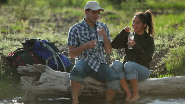 Backpackers take break by stream and drink water video