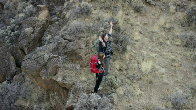 Backpacking couple hiking in a canyon wilderness video