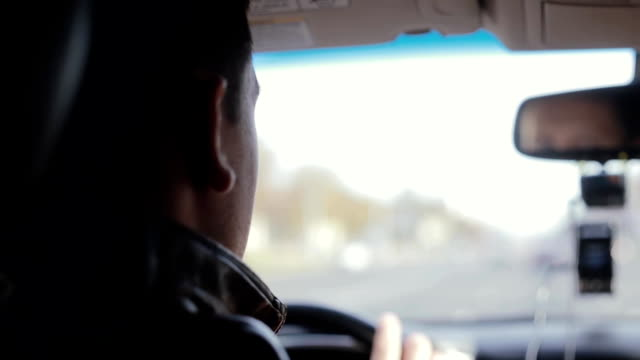 Backview of a man driving a car. Traveling by car video