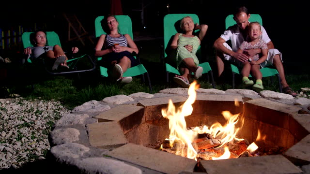 Backyard patio area with stone fire pit people looking at flame relaxing video