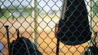 Bags hanging from fence inside dugout at baseball field video