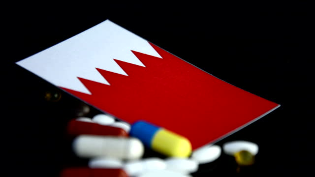 Bahrain flag with lot of medical pills isolated on black background video