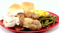 Baked chicken plated with vegetables and rolls. Right rotation Wide Shot. video