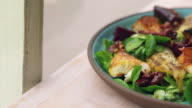 Baked goats cheese and pear salad by a window, close up pan video