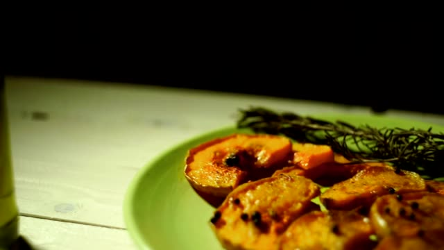Baked pumpkin slices with rosemary herb. Baked pumpkin pieces video