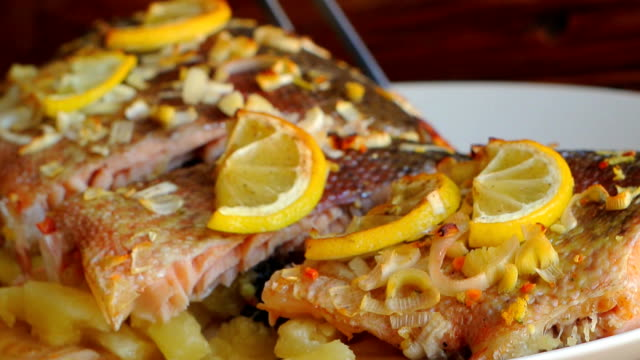 Baked salmon with pineapple and slices of lemon on a plate on a video
