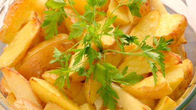 baked sliced potatoes with sprig of parsley video