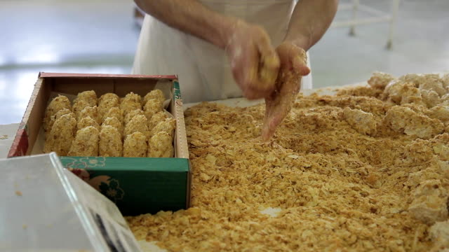Baker boned pieces of dough in bread crumbs and packs in a box video